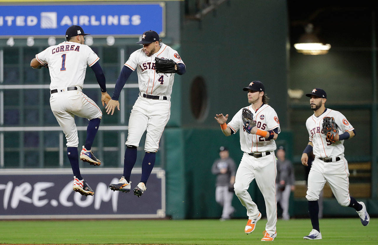The Astros' Carlos Correa and George Springer celebrate after beating the Yankees 7-1 in Game 6 of the American League Championship Series on Oct. 20, 2017, in Houston. (AP Photo/David J. Phillip)