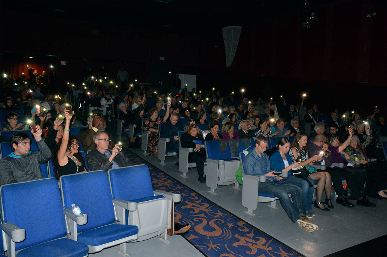 """Over 300 people lift cellphone lights to celebrate the conclusion of a Baha'i Light of Unity Festival, held Oct. 21 at the Northwest Music Hall in Everett. The event celebrated the 200th anniversary of the birth of the founder of the Baha'i faith. A follow-up activity, a showing of the documentary """"Light to the World,"""" is planned for 4-6 p.m. Nov. 18 at the Hall, located inside the Everett Mall. (Contributed photo)"""