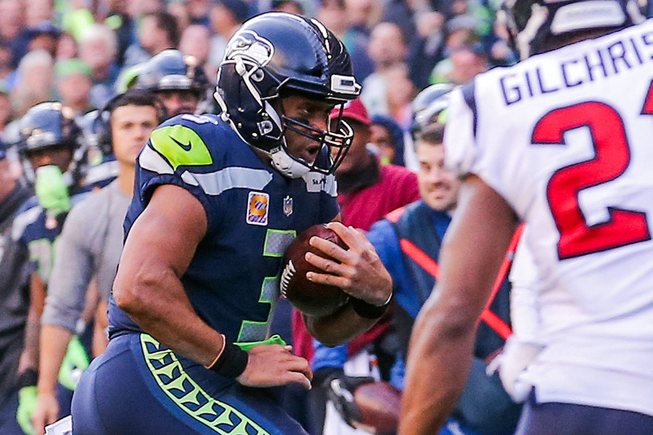 Russell Wilson was the Seahawks' leading rusher Sunday, with 30 yards on four carries. (Kevin Clark / The Herald)