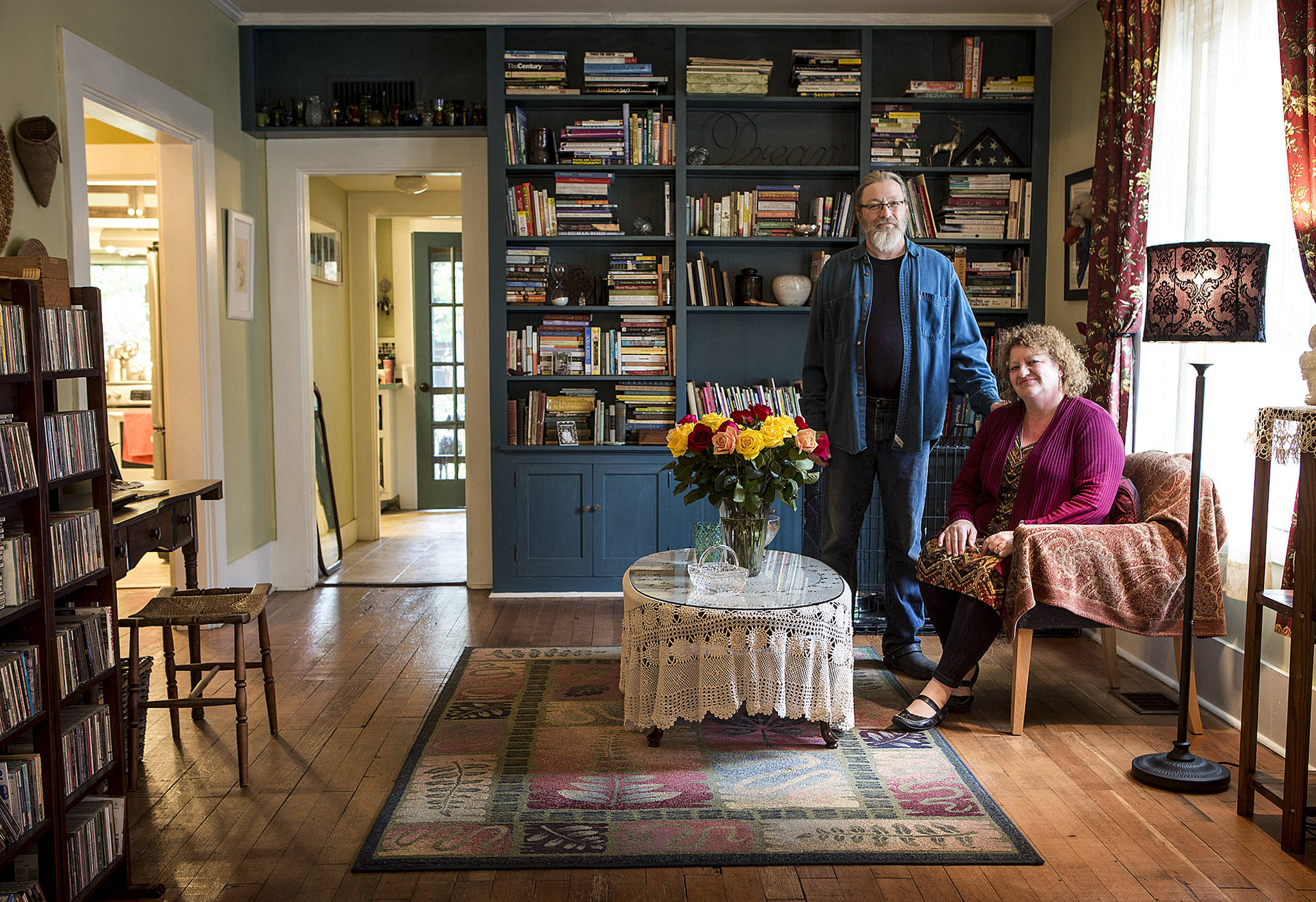 Wendy Keene and Tim Schultz get cozy in their Monroe home . The couple renovated the house, originally built in 1903, while keeping many of its charms. (Ian Terry / The Herald)