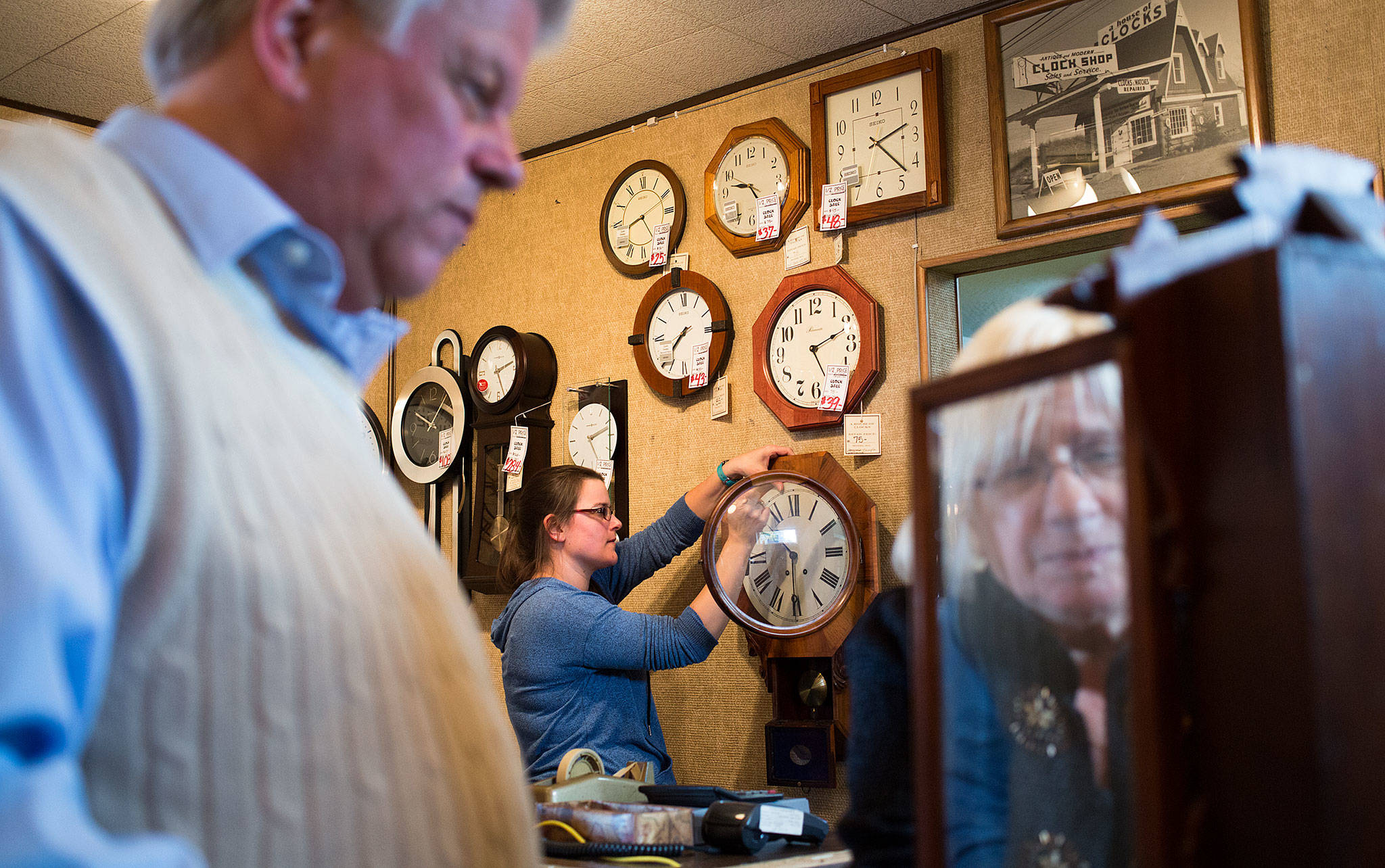 Crystal Rice works on a customer's clock as owner Susie Hennig (right) winds a time-and-strike clock brought in by Steve Heath at A House of Clocks on Monday in Lynnwood. The landmark Lynnwood shop plans to close after more than 54 years. David Nofziger said he and his siblings, who took over the business from their parents, are closing the shop because they're reaching retirement age. (Andy Bronson / The Herald)