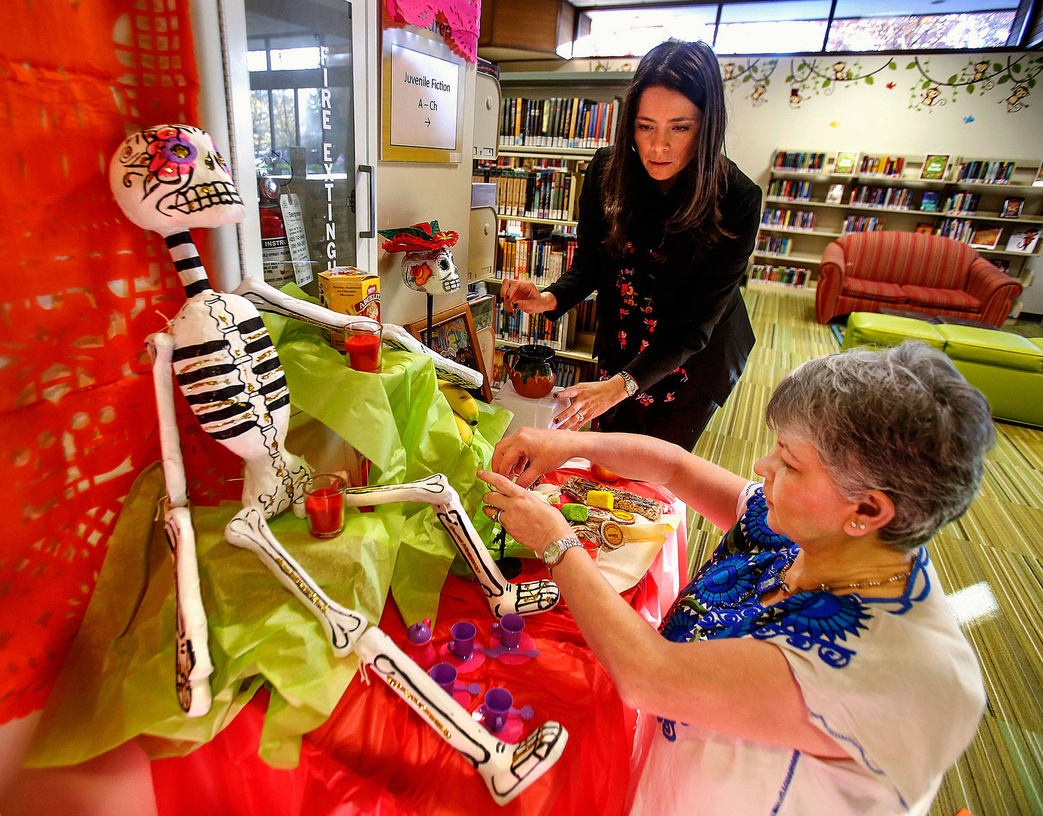 At Lynnwood Library, Julieta Altamirano-Crosby (left) and Maria Casey create a Day of the Dead display in the children's area Tuesday. The women created a larger adult version as well. (Dan Bates / The Herald)