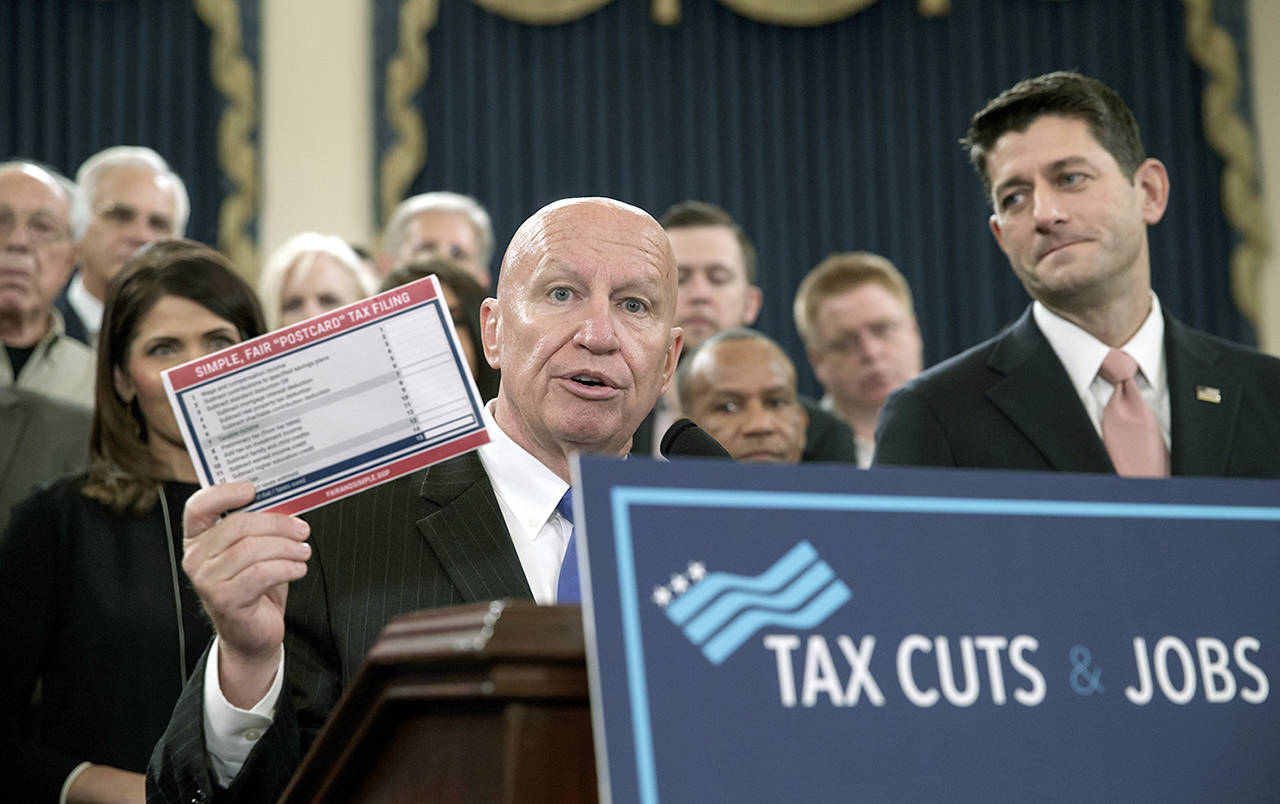 """House Ways and Means Committee Chairman Kevin Brady, R-Texas, joined by Speaker of the House Paul Ryan, R-Wis., holds a proposed """"postcard tax filing form"""" as they unveil the GOP's far-reaching tax overhaul, the first major revamp of the tax system in three decades, on Capitol Hill in Washington on Thursday. (AP Photo/J. Scott Applewhite)"""