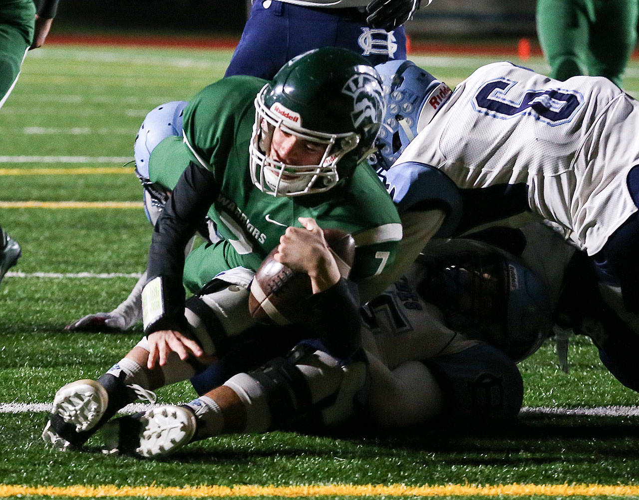 Edmonds-Woodway's Reilly Chappell rolls over Gig Harbor's Brenden Rivera for a touchdown Friday at Edmonds Stadium. (Kevin Clark / The Herald)
