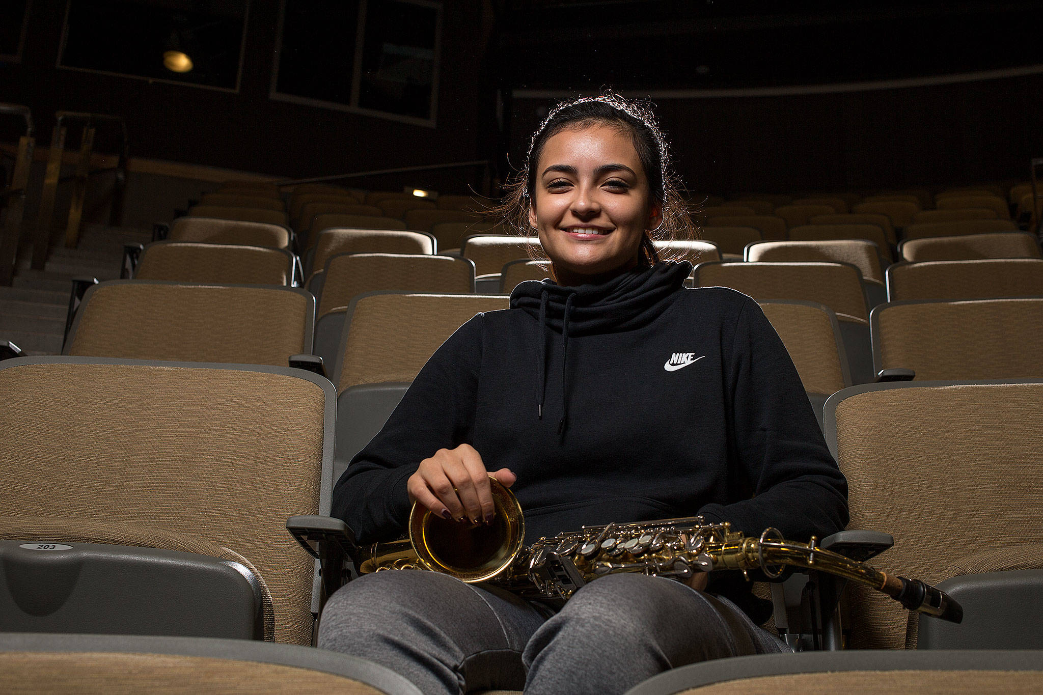 Lynnwood High School senior Venecia Lucio sits with her saxophone in school's theater Nov. 8. Lucio has led fundraisers as part of her work with Colores Unidos, which celebrates Latino and Spanish-speaking cultures. (Andy Bronson / The Herald)