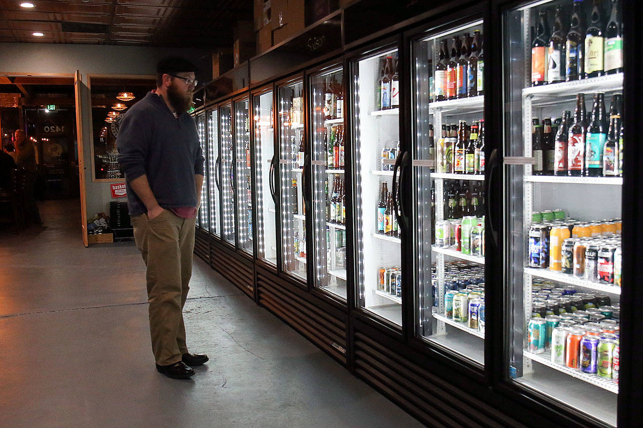 Daniel Howe browses the more than 550 different beers available at Toggle's. (Kevin Clark / The Herald)