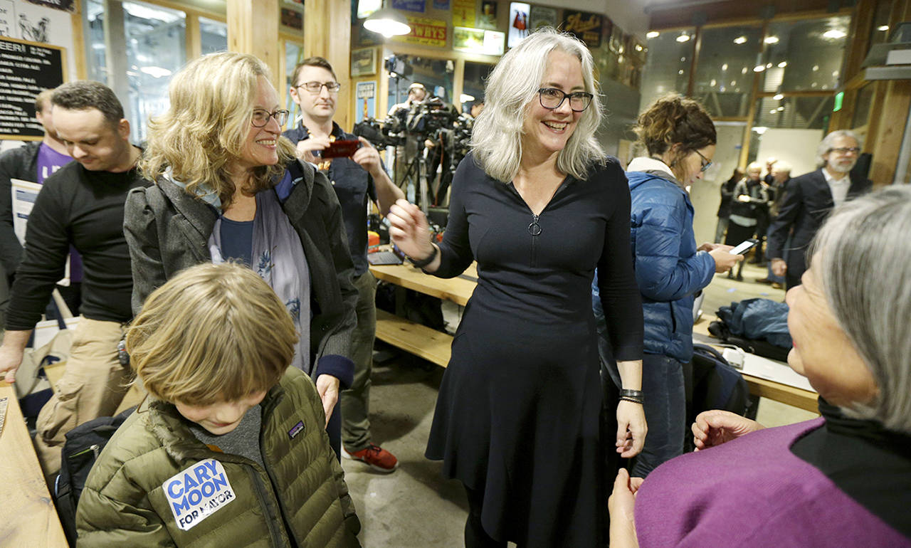 Seattle Mayoral candidate and urban planner Cary Moon (right) talks with supporters during an election night gathering Tuesday in Seattle. (AP Photo/Ted S. Warren)