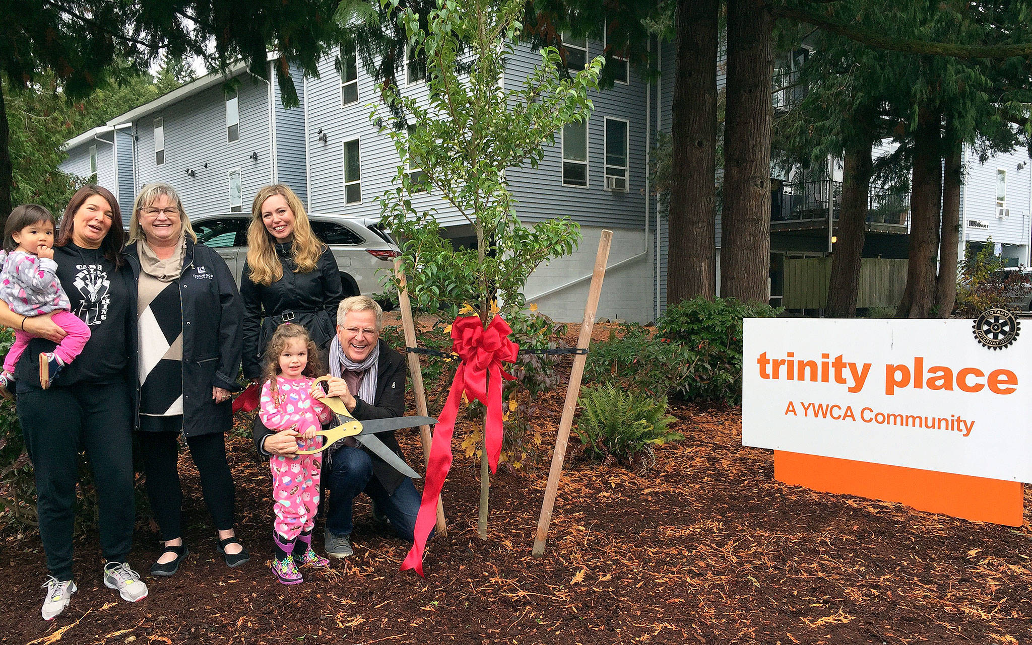 Rick Steves (right) at Trinity Place, the Lynnwood property he donated this year to YWCA Snohomish County. He was joined by (from left) Trinity Place resident Ricanna (holding child), Lynnwood Mayor Nicola Smith and YWCA Executive Director Mary Anne Dillon. (Contributed photo)