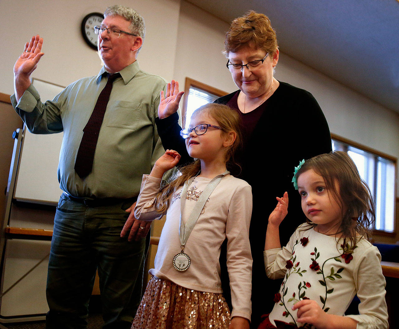 David and Kellie Preston of Everett, Sabrina, 7, and Savannah, 4, raise their right hands and make a pledge before Snohomish County Superior Court Judge David Kurtz. David Preston is already wearing the ring on his right hand that he used to make a pledge to his wife that he would bring up his two grandchildren. The couple adopted the girls Friday. (Dan Bates / The Herald)