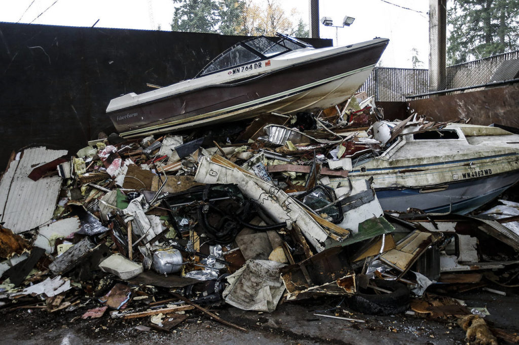 A boat sits atop a pile of trash at the Cathcart transfer station. (Ian Terry / The Herald)