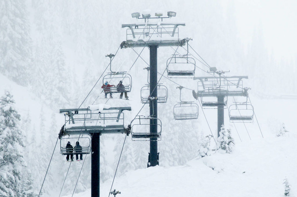 Skiers and snowboarders make their way up the Skyline Express chairlift at Stevens Pass on Thursday. (Ian Terry / The Herald)