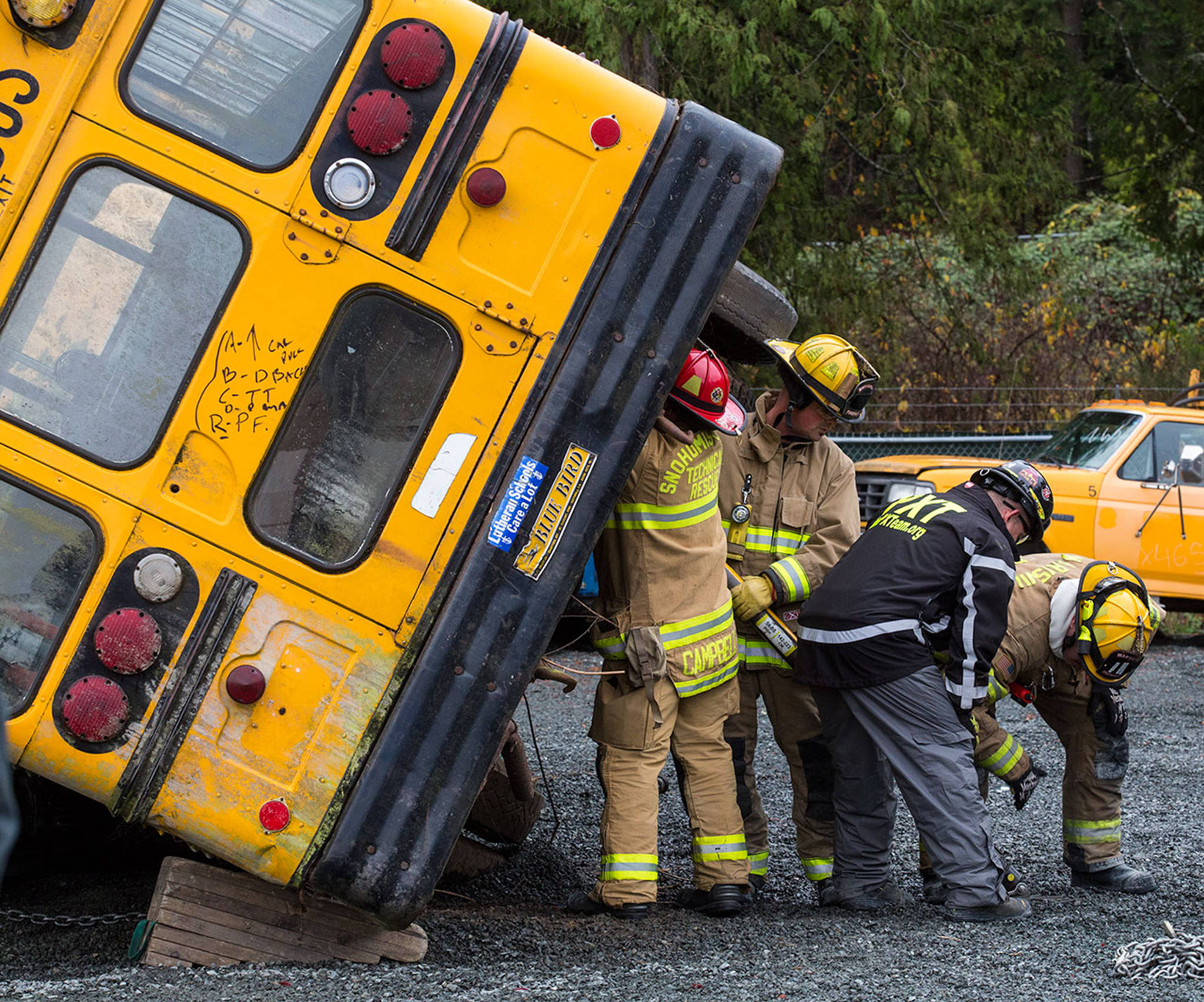 Snohomish county area firefigfhters brace and stabilize a rolled bus as they practice multi-agency response training for vehicle accidents at NW Auto Recyclers on Nov. 15 in Lake Stevens. (Andy Bronson / The Herald)