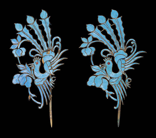 Blue kingfisher feathers embellish this Chinese hair pin. It has phoenix birds with flame-shaped tails and irises as part of the design. The pair sold for $854.