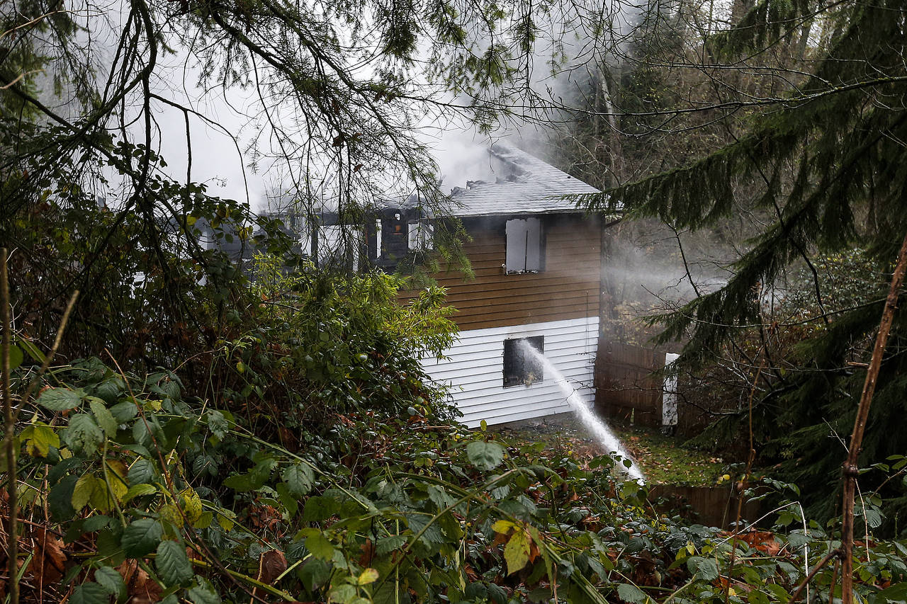 A home in Lynnwood where a man was found dead in his garage burns on Wednesday. (Ian Terry / The Herald)