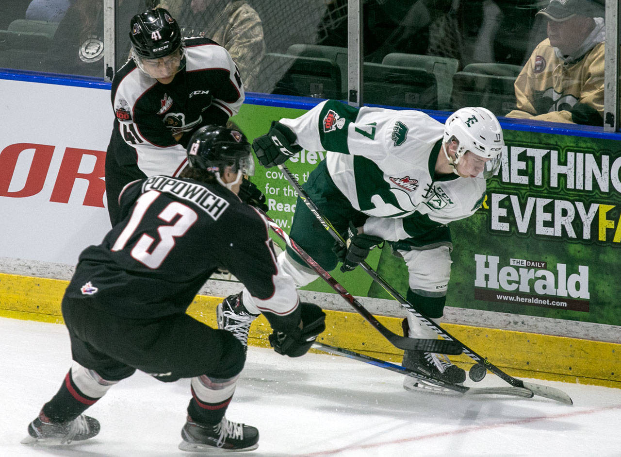The Silvertips' Matt Fonteyne (right) controls the puck with Vancouver's Alex Kannok Leipert (left) and Tyler Popowich giving chase in the first period of a game Dec. 29, 2017, at Angel of the Winds Arena in Everett. (Kevin Clark / The Herald)