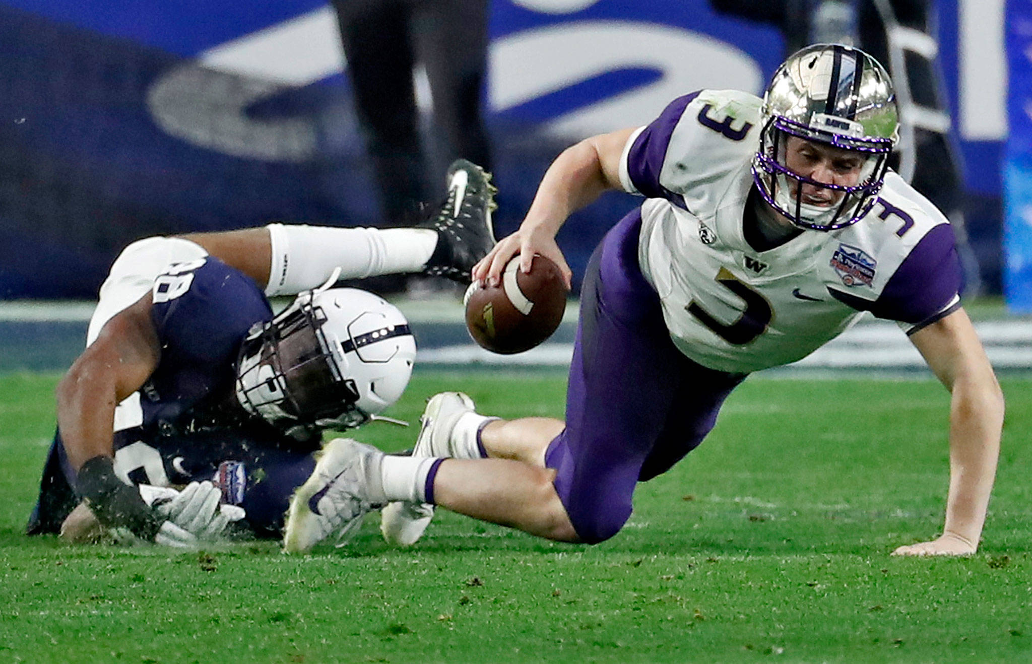 Washington quarterback Jake Browning (3) is tripped up by Penn State defensive end Shareef Miller (48) during the second half of the Fiesta Bowl on Dec. 30, 2017, in Glendale, Ariz. (AP Photo/Rick Scuteri)