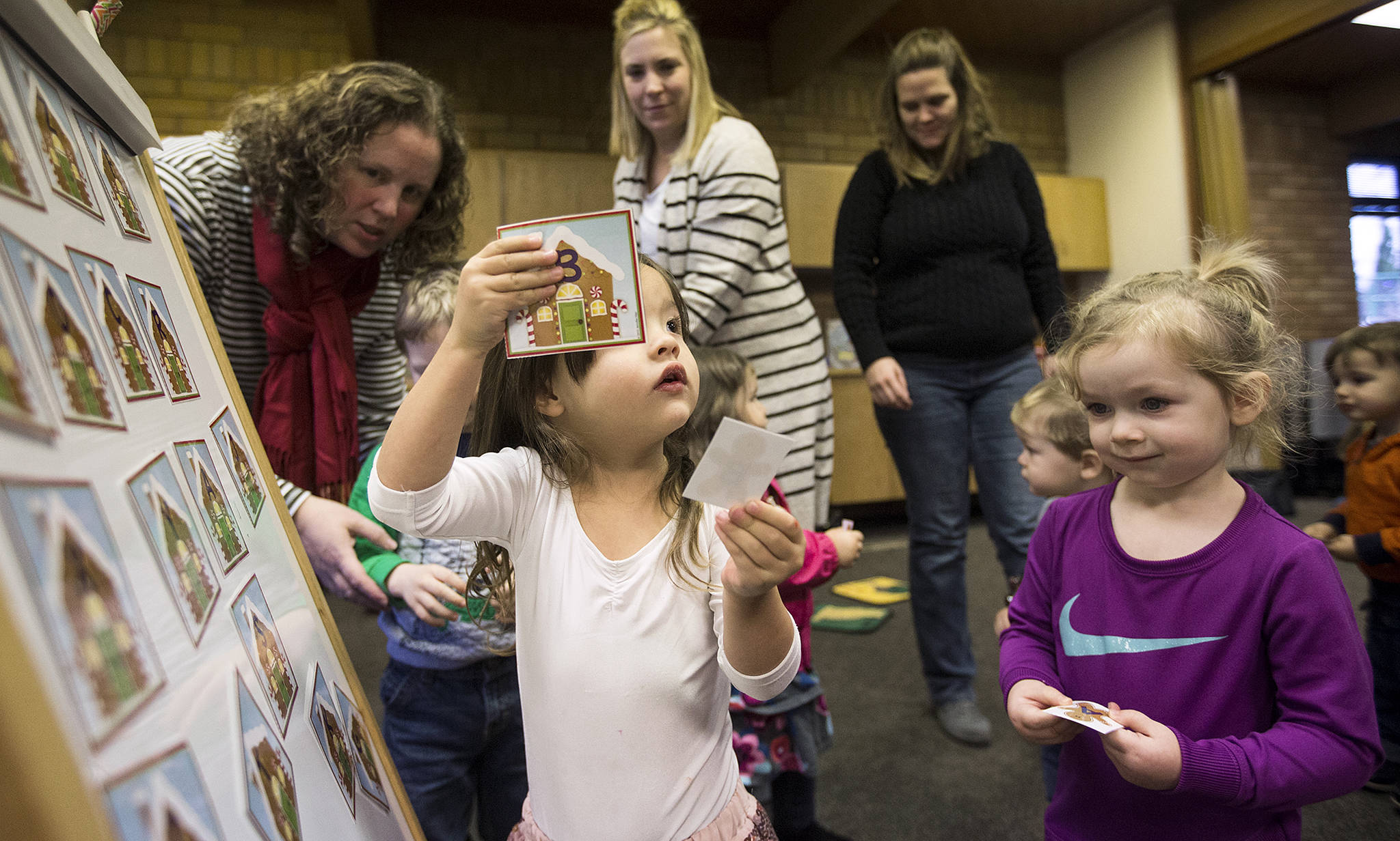 Harper Ninaud, 3, holds up her matching letters as parents and their toddlers enjoying reading, songs and activities at the Lake Stevens Library on Dec. 19. (Andy Bronson / The Herald)