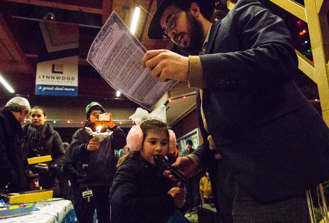 Rabbi Berel Paltiel holds the microphone so his 5-year-old daughter, Chaya Paltiel, can sing Chanukah songs at a celebration for the Festival of Lights during the fifth annual public Menorah Lighting Ceremony at Lynwood City Hall on Dec. 26 of last year. Nearly 50 gathered to sing, eat and celebrate the third night of Chanukah. (Daniella Beccaria / Herald file)