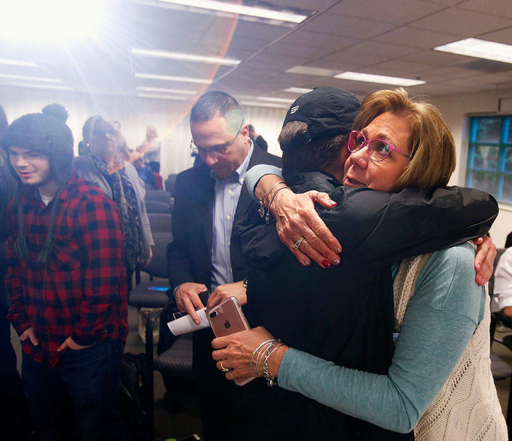 Parker Lang's mom, Vicki Moore hugs her son's best friend, Logan McGill, 20 as Thursday's event nears an end. McGill had contributed a short movie and slide show that portrayed Parker's upbeat personality and joy he shared with others. (Dan Bates / The Herald)