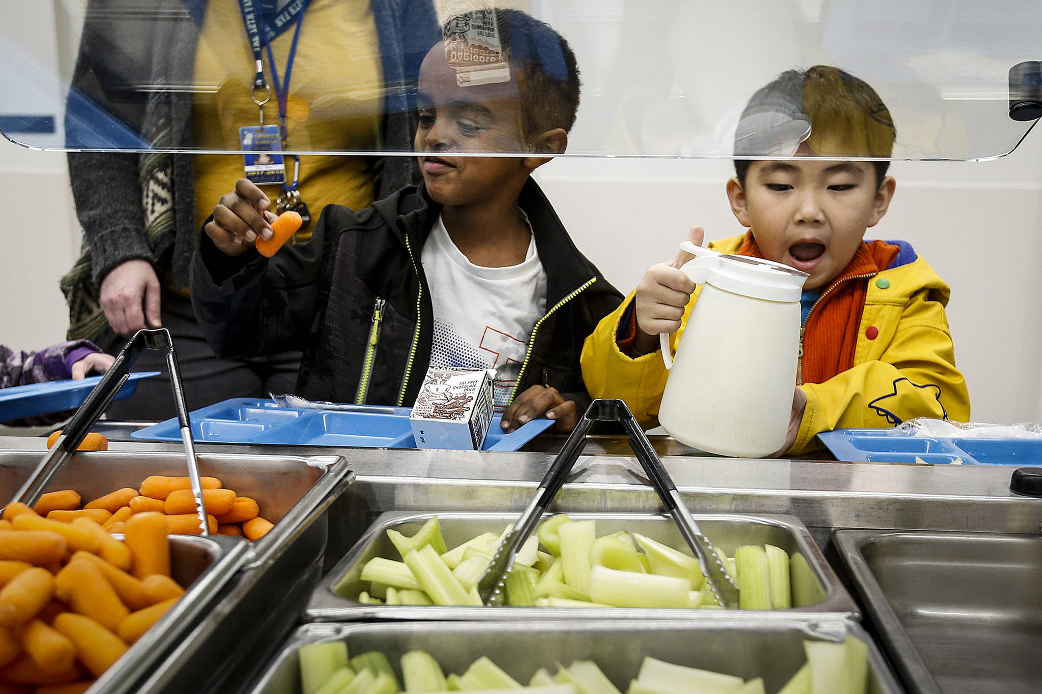 Kindergartner Maereg Andualem (left) checks out a carrot while fellow classmate Alex Shim helps himself to some dressing during lunchtime at Lynndale Elementary School in Lynnwood on Thursday, Nov. 30. (Ian Terry / The Herald)