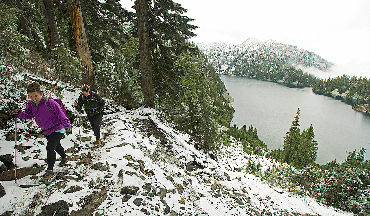 In this Nov. 3, 2015, file photo, Kasee Palmer, left, and Summer Sturhan hike on Snow Lake Trail above Snoqualmie Pass in Washington state. (AP Photo/Ted S. Warren, File)