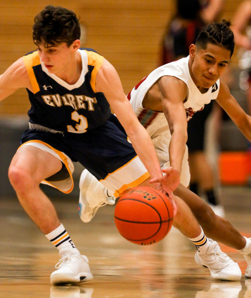 Cascade's Luke Wugumgeg attempts a steal from Everett's Preston Campbell on Friday night at Everett Community College. (Kevin Clark / The Herald)