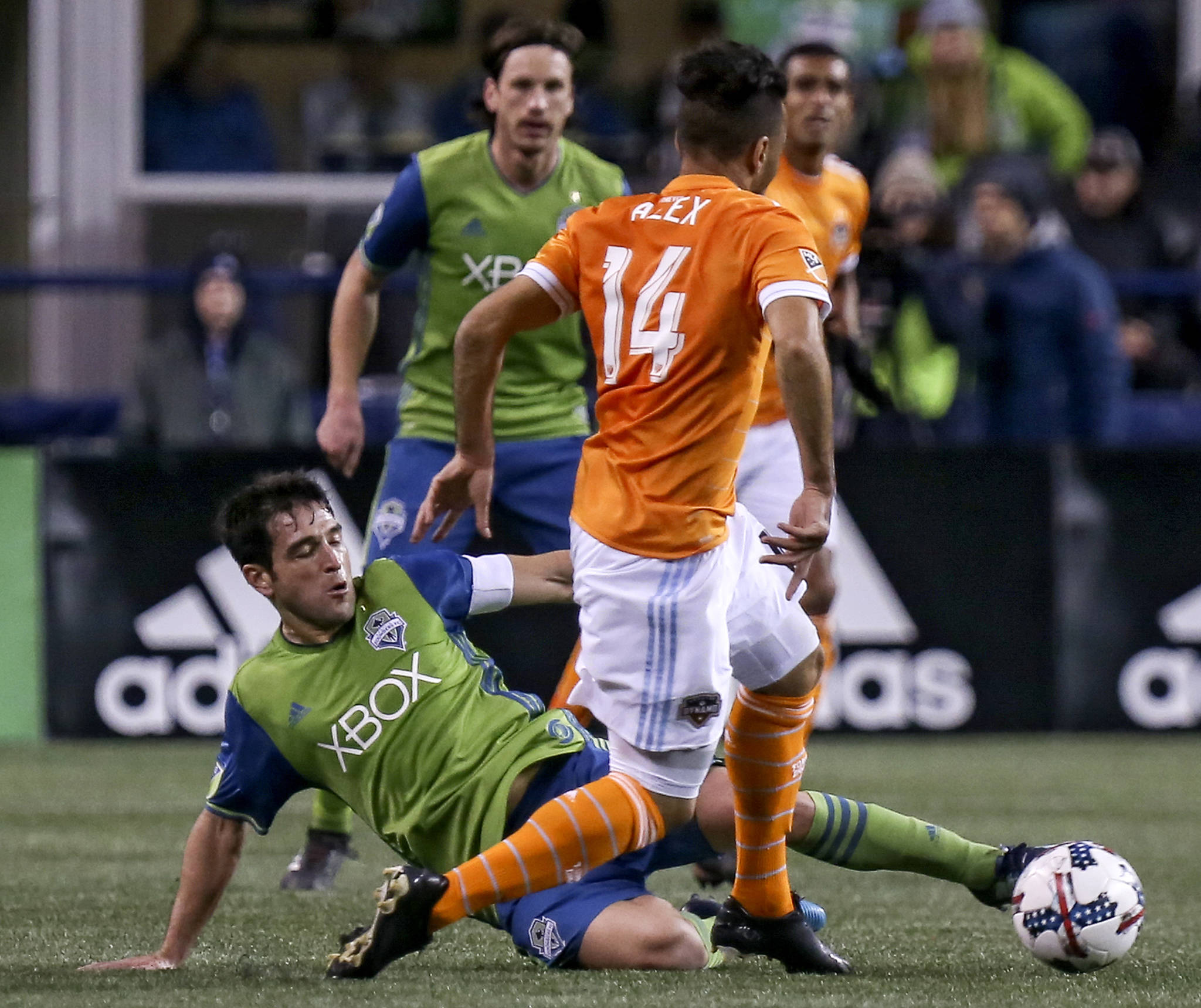 Seattle's Nicolas Lodeiro slides to dislodge the ball from Houston's Alex in the first half of the Western Conference Finals at CenturyLink Field in Seattle on Nov. 30. (Kevin Clark / The Herald)