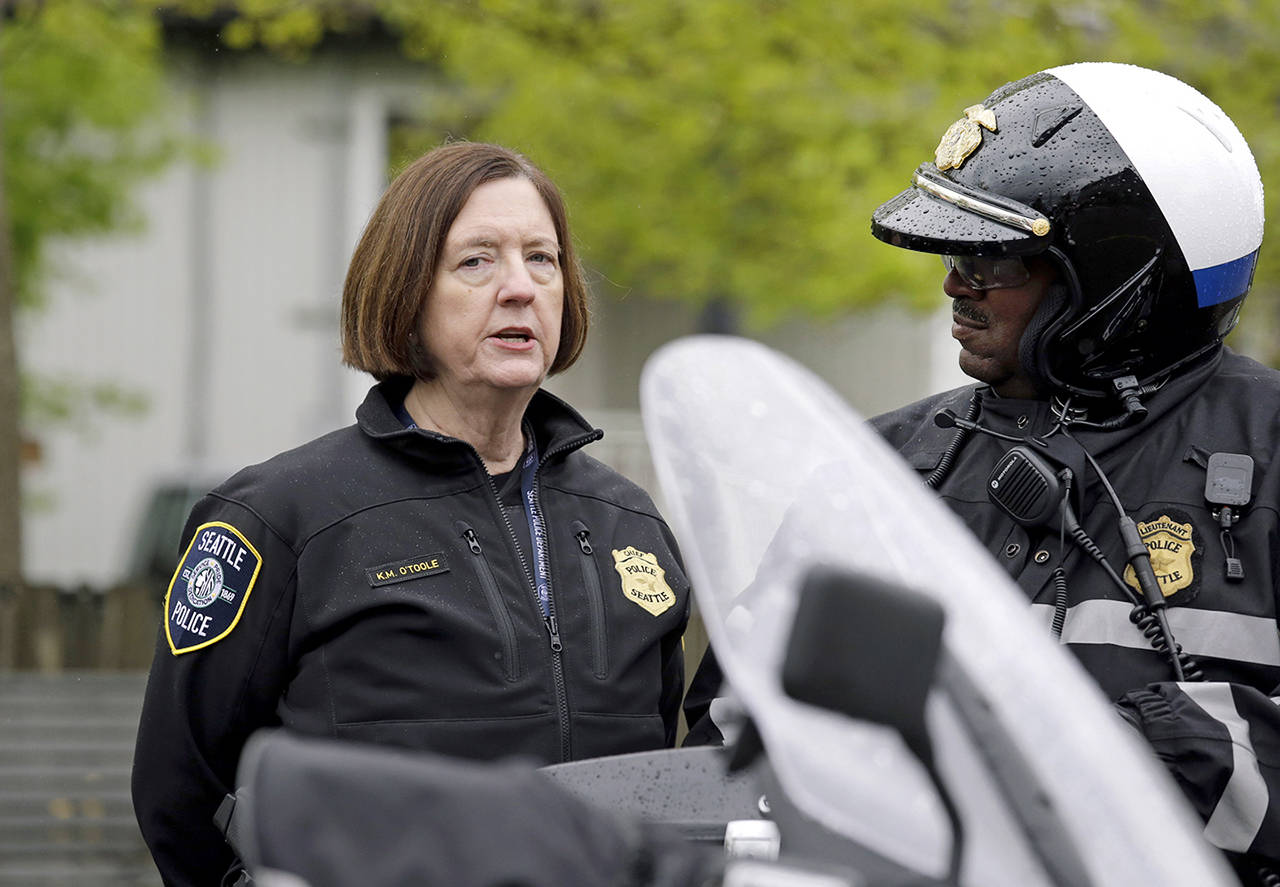 In this May 1 photo, Seattle Police Chief Kathleen O'Toole (left) talks with an officer before a march for worker and immigrant rights at a May Day event in Seattle. (AP Photo/Elaine Thompson, File)