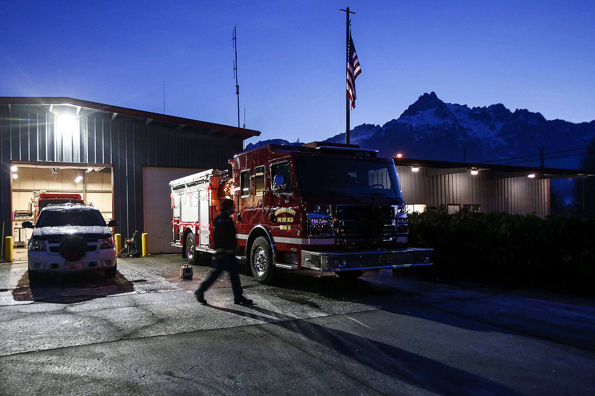 Darrington Fire Capt. Drew Bono walks in front of engine 38 as Whitehorse Mountain glows faintly in the evening light on Tuesday, Dec. 12. Darrington is one of Snohomish County's few towns that rely on a true volunteer fire department. (Ian Terry / The Herald)