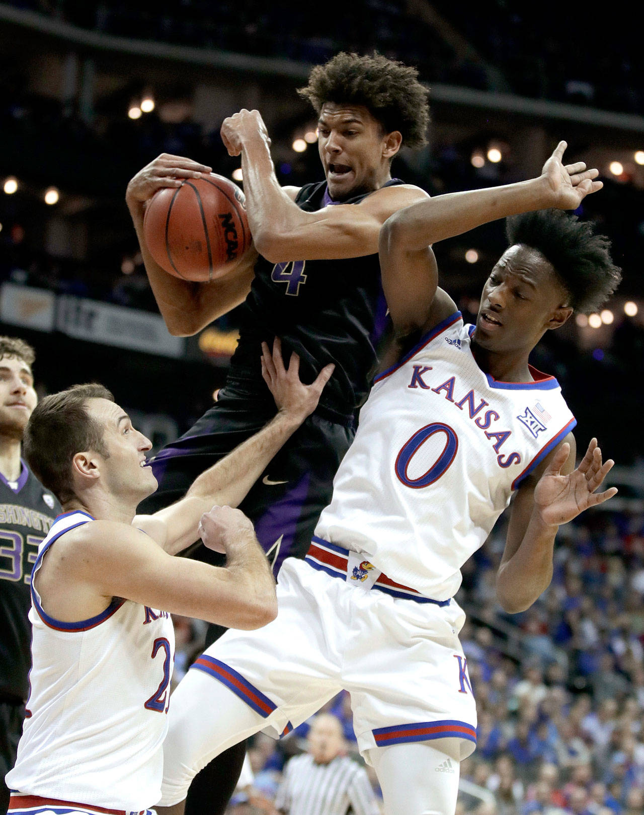 Washington's Matisse Thybulle (center) beats Kansas' Clay Young (left) and Marcus Garrett (0) to a rebound during the first half of a game Dec. 6, 2017, in Kansas City, Mo. (AP Photo/Charlie Riedel)