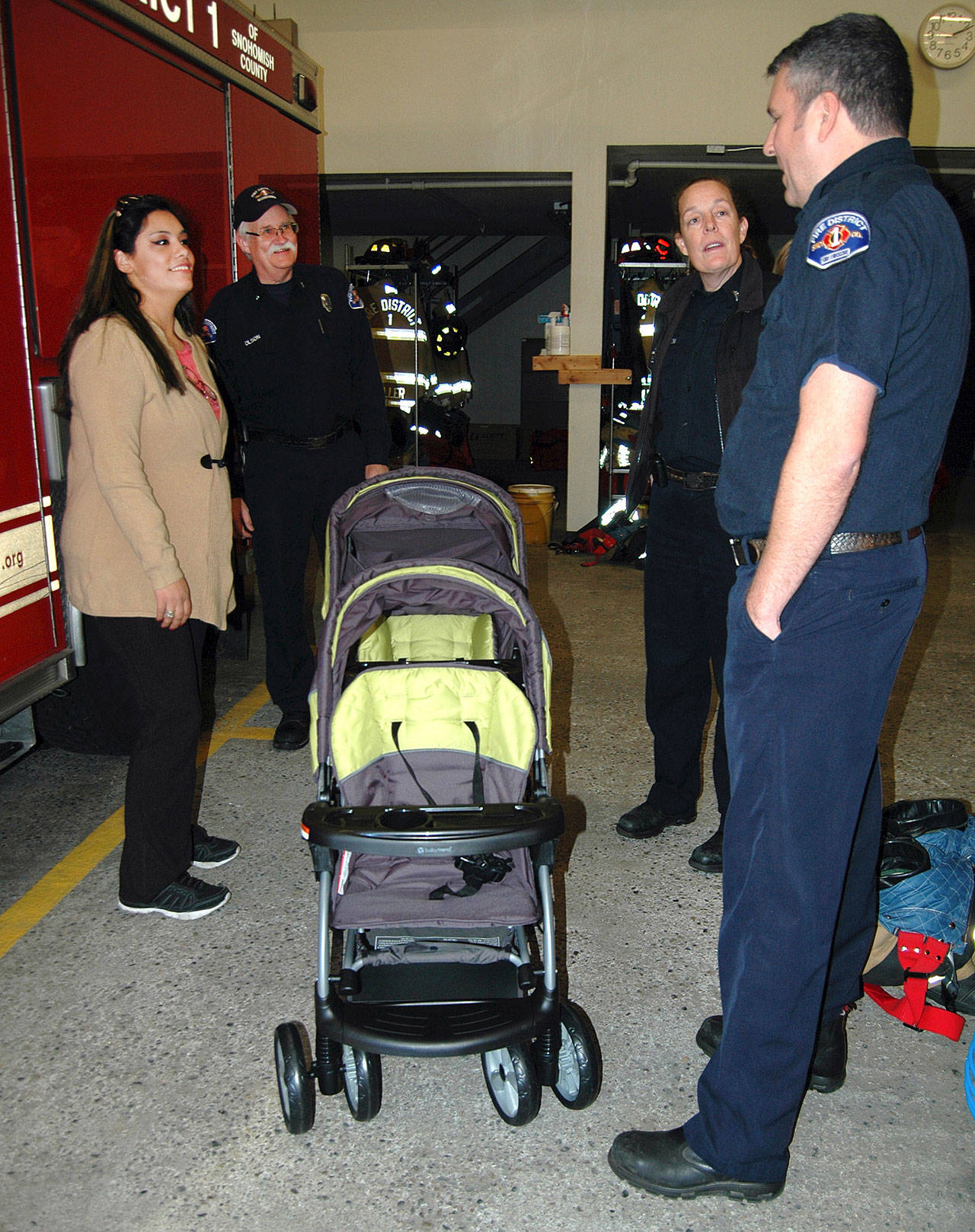 The crew of South Snohomish Fire and Rescue Medic 13 presents Johanna Castillo with a new stroller, days after her old one was destroyed in a crash near Mill Creek. (South Snohomish Fire and Rescue)