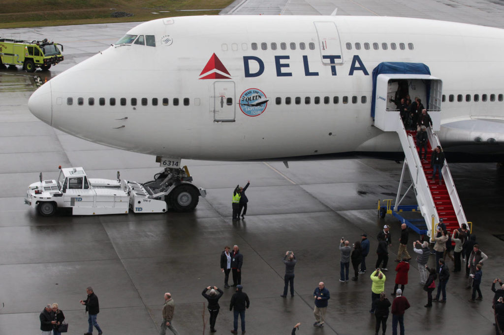 VIPs, Delta Air Lines employees and other passengers disembark from o0ne of the airline's last 747s at the Future of Flight Aviation Center at Paine Field during a stop on the plane's a farewell tour on Monday. (Andy Bronson / The Herald)