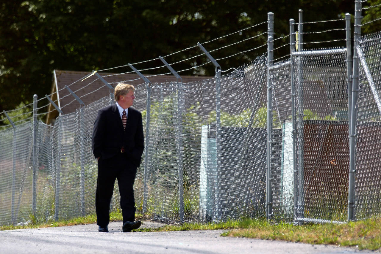 Between rows of chainlink fence topped with barbed wire, Mayor Ray Stephanson walks down a longtime quarantined street in the infamous ASARCO cleanup area in north Everett on June 15, 2004. (Dan Bates / Herald file)