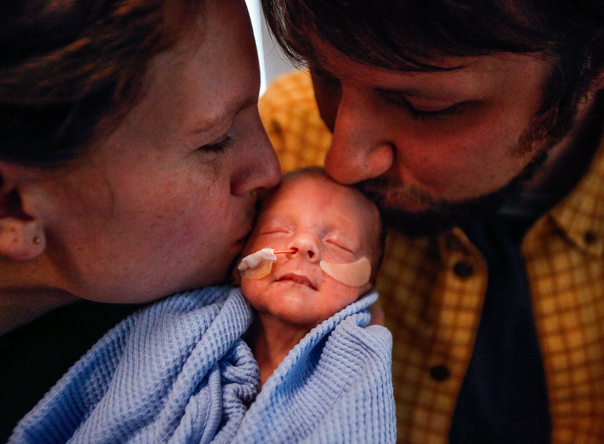 Elisabeth Strom and husband Steve Strom of Marysville kiss their son, Hugo, who was born on the way to the hospital Dec. 2, at 30 weeks. He weighed 3 pounds, 11.6 ounces. Hugo is in neonatal intensive care for several more weeks. (Dan Bates / The Herald)