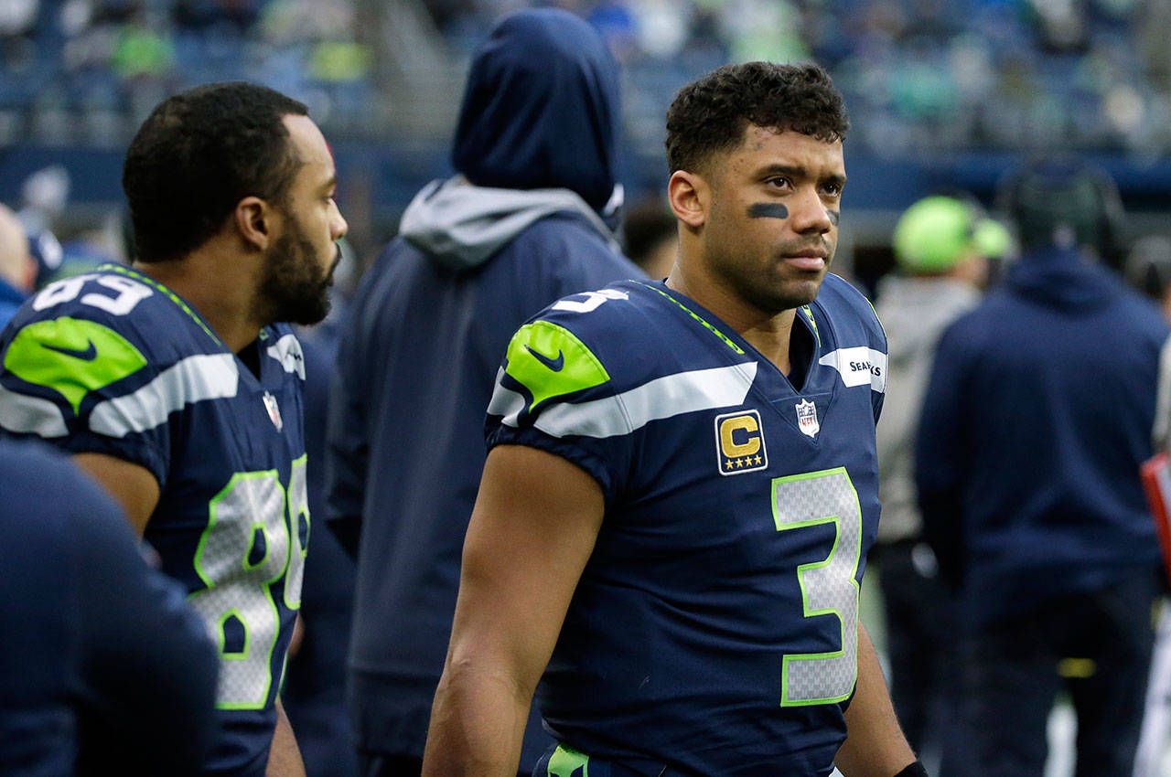 Seattle Seahawks quarterback Russell Wilson (righ) and wide receiver Doug Baldwin (left) stand on the sideline during the second half of Sunday's NFL game in Seattle. (AP Photo/Elaine Thompson)