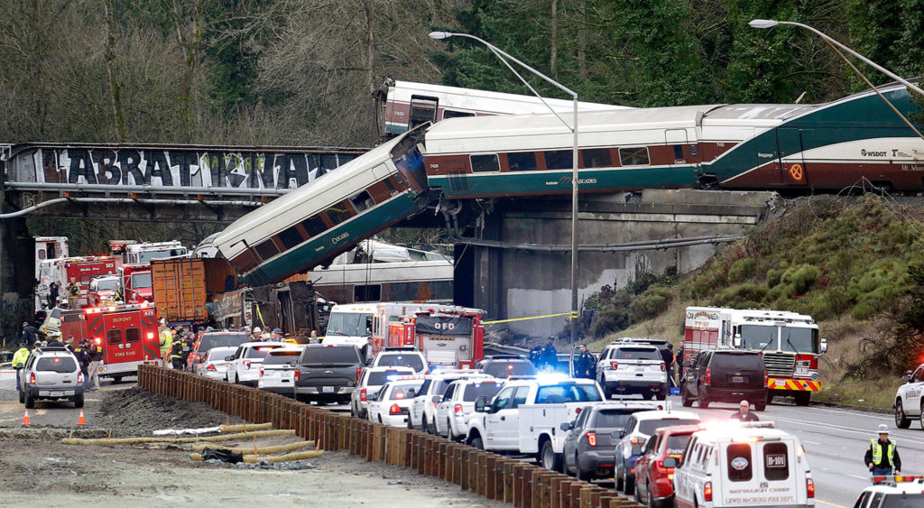Some cars of an Amtrak train are spilled onto I-5 and some remain on the tracks above on Monday near DuPont. (AP Photo/Elaine Thompson)