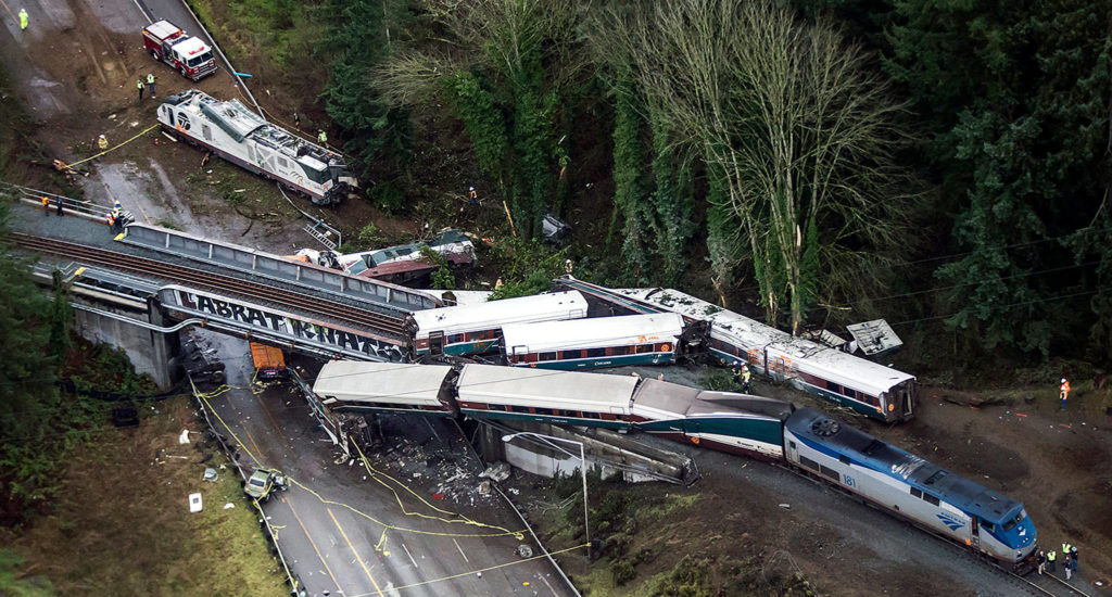Cars from an Amtrak train that derailed lie spilled onto I-5 on Monday. (Bettina Hansen/The Seattle Times via AP)