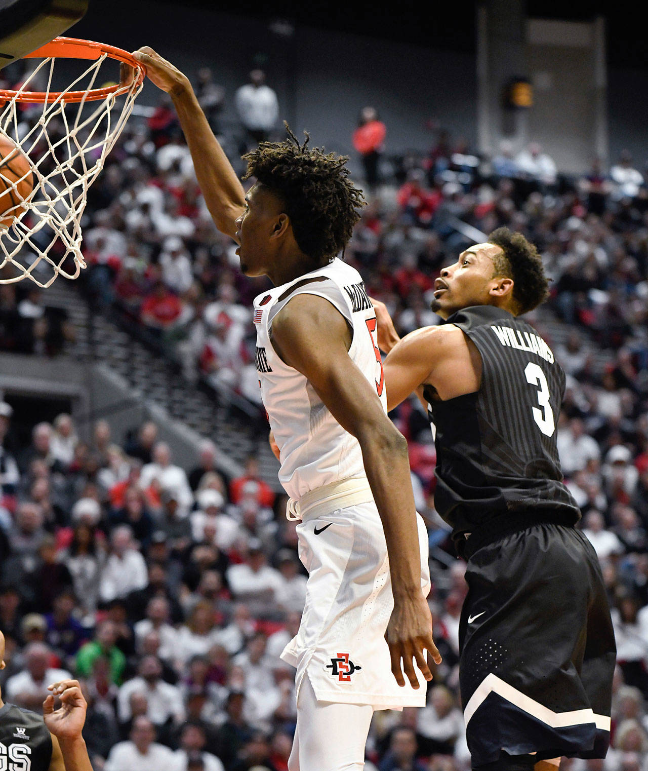 San Diego State forward Jalen McDaniels (5) tips in a rebound in front of Gonzaga forward Johnathan Williams (3) during the second half of a game Thursday in San Diego. (AP Photo/Denis Poroy)