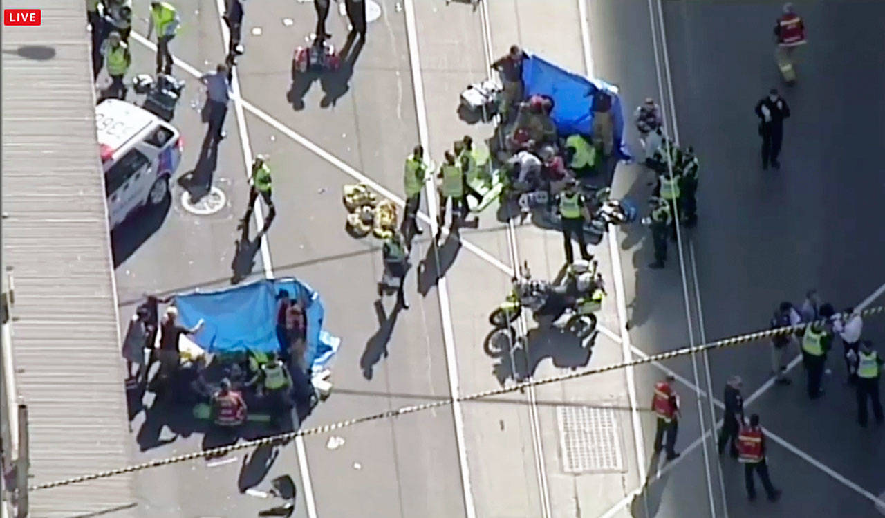 Emergency medical workers offer aid to victims struck by a vehicle in Melbourne, Australia, on Thursday. (Australian Broadcast Corp. via AP, File)