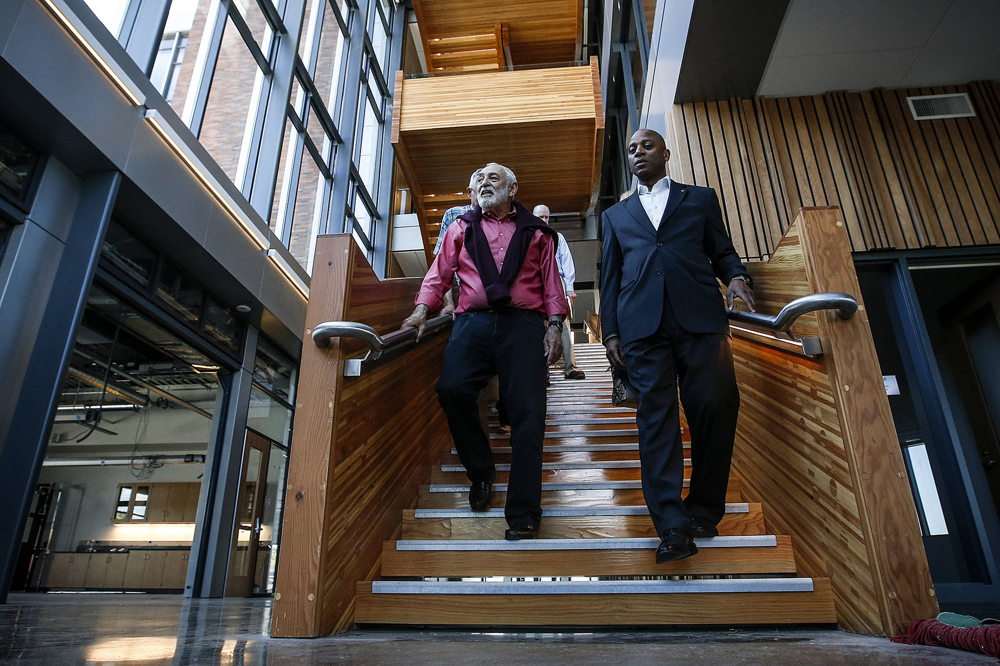 Dr. Larry Schecter (left), associate dean for WSU North Puget Sound's medical education programs, walks down the central staircase with Chancellor Paul Pitre at Washington State University Everett. The campus, which opened in 2017, will attract youth and talent to Everett and Snohomish County. (Ian Terry / The Herald)