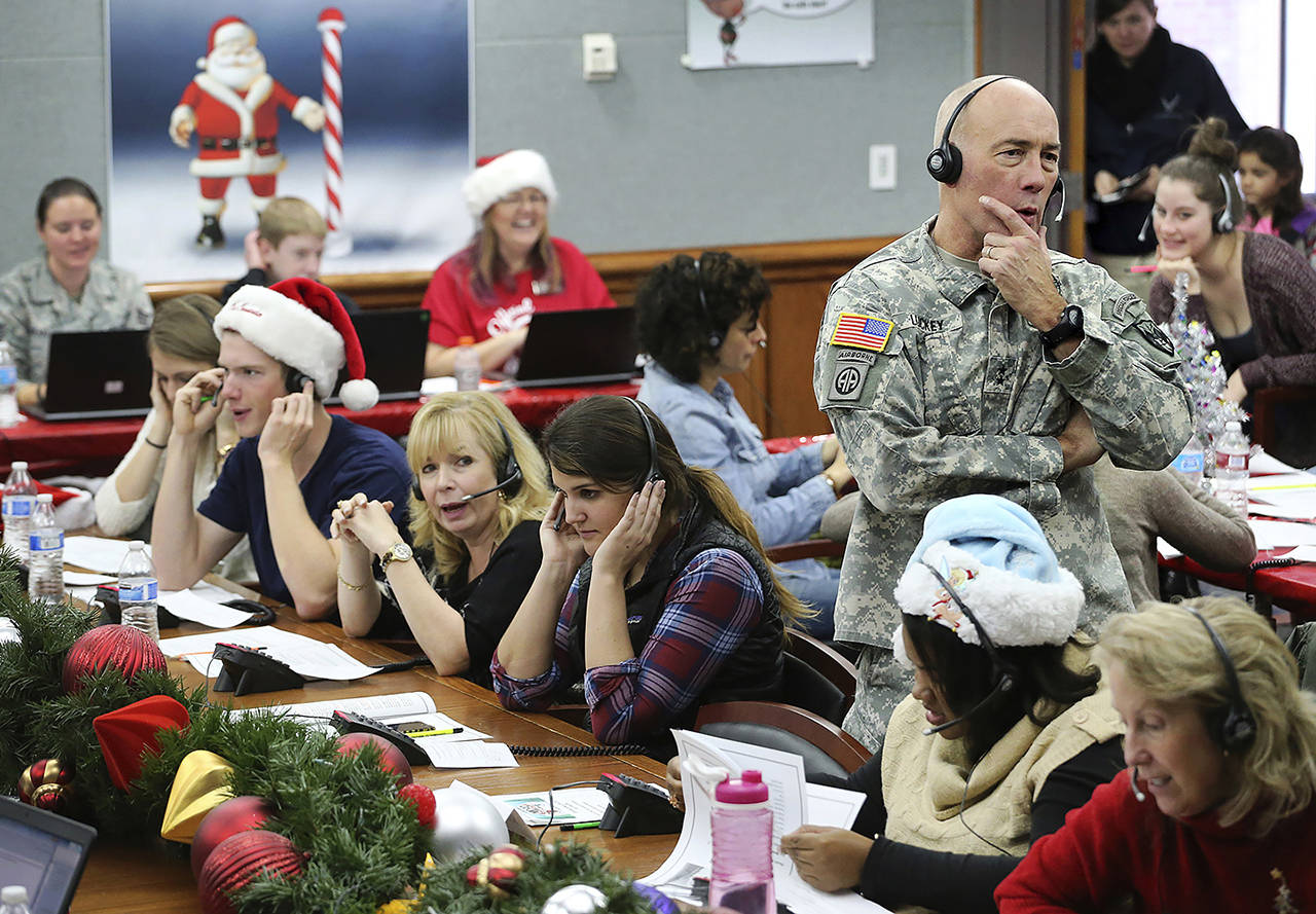 In this Dec. 24, 2014, photo, NORAD and USNORTHCOM Chief of Staff Maj. Gen. Charles D. Luckey joins other volunteers taking phone calls from children around the world asking where Santa is and when he will deliver presents to their homes, inside a phone-in center during the annual NORAD Tracks Santa Operation, at the North American Aerospace Defense Command, at Peterson Air Force Base, Colorado. (AP Photo/Brennan Linsley, File)