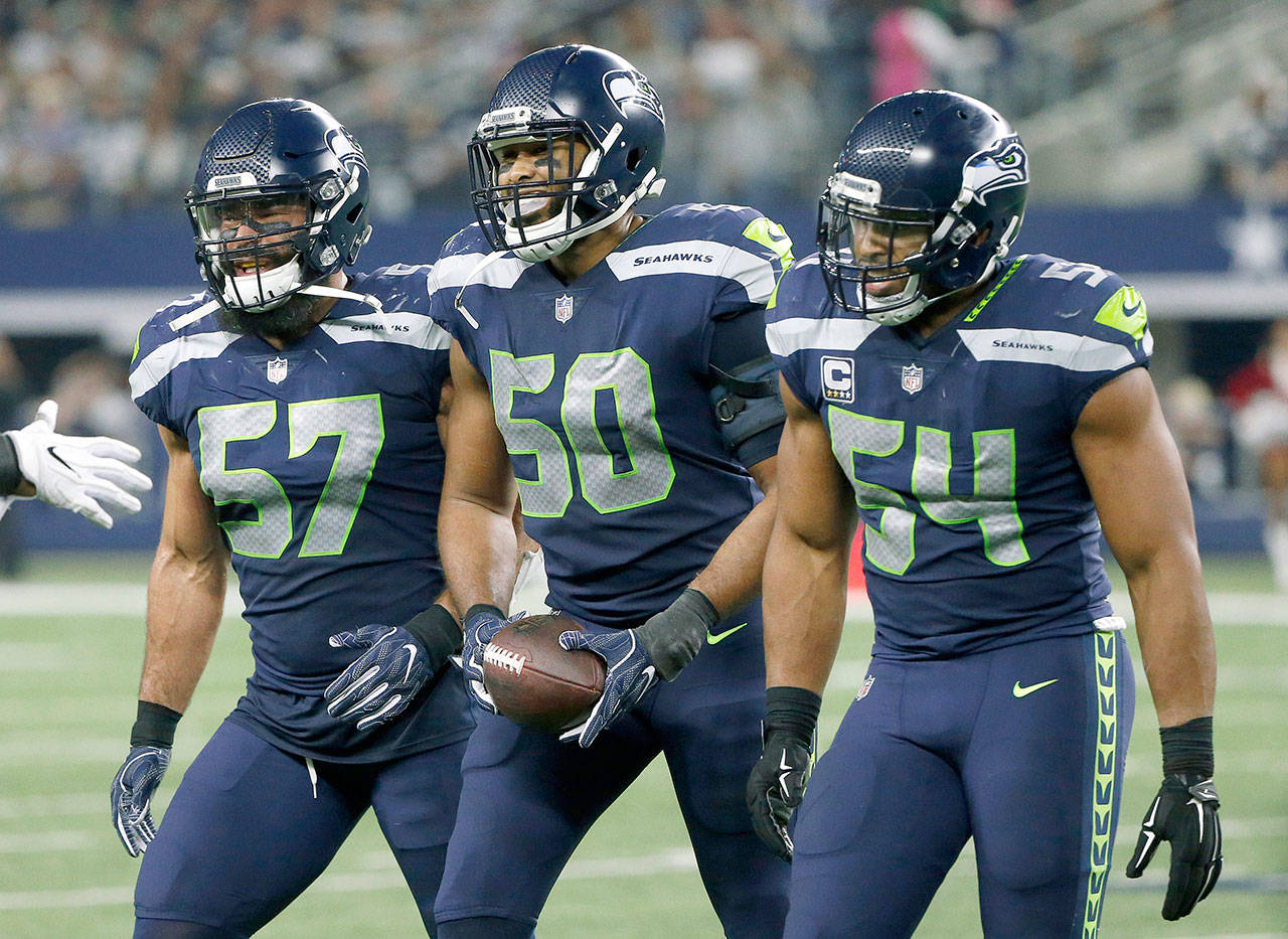 Seattle's K.J. Wright (50) celebrates his interception that preserved the Seahawks' lead in the third quarter of a 21-12 victory over Dallas on Sunday in Arlington, Texas. (AP Photo/Michael Ainsworth)