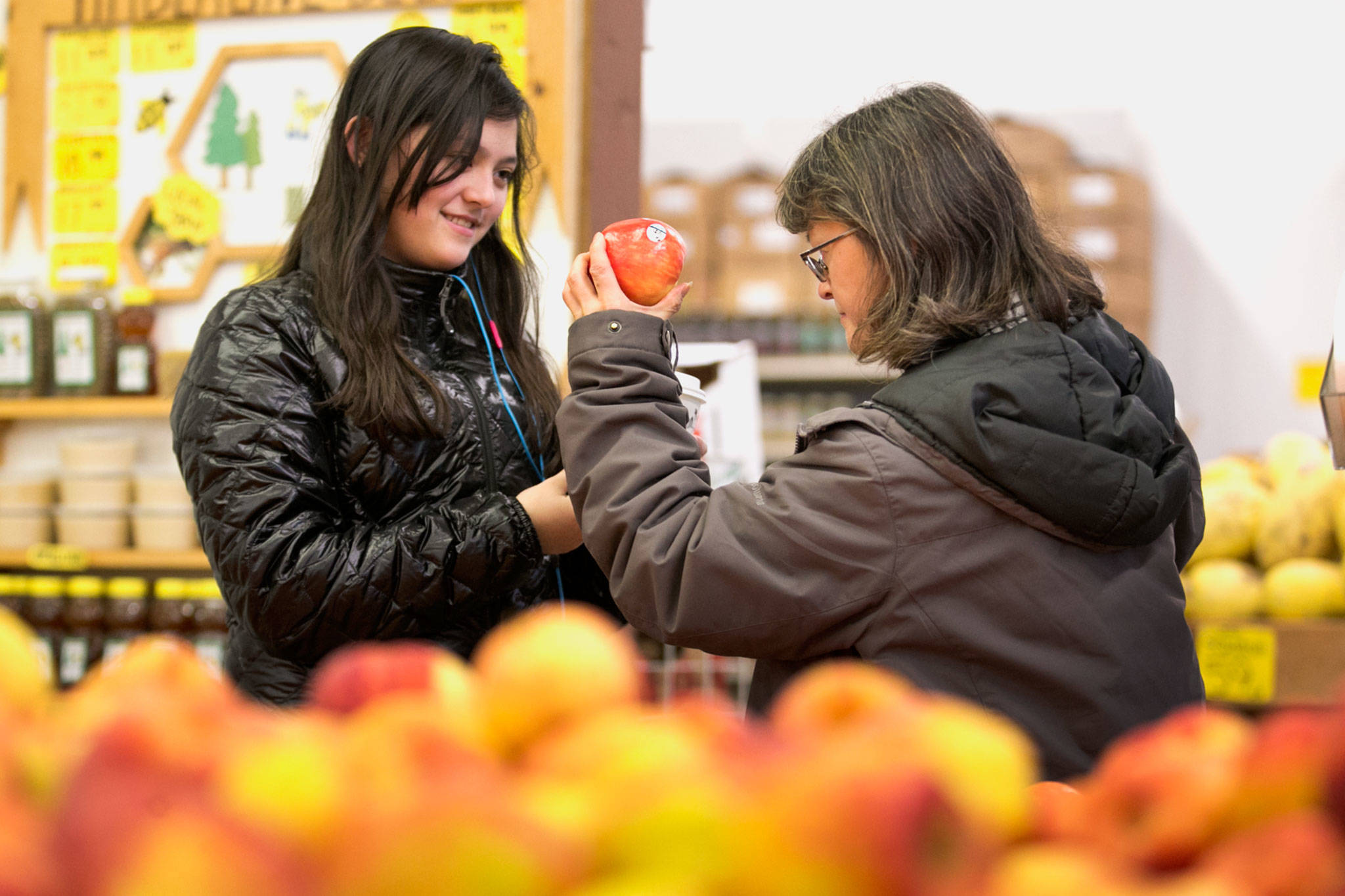 Olivia Nishimoto (left) and her mother, Ginger Nishimoto, browse apples Thursday night at Produce Place in Marysville. (Kevin Clark / The Daily Herald)