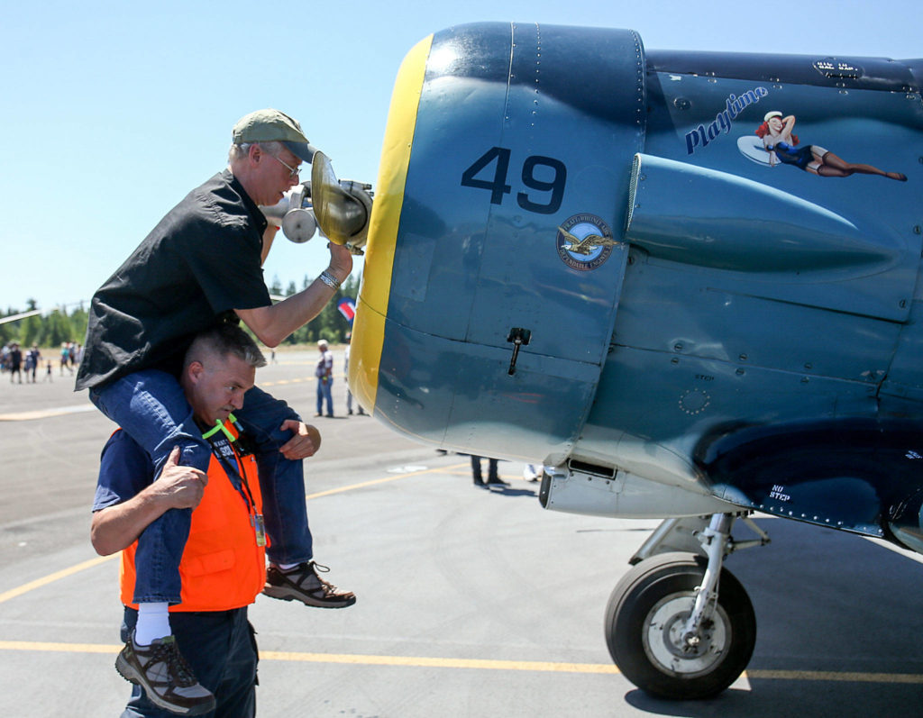 George Slocum sits on Brandon Edwards' shoulders as he wipes down a propellor during the Arlington Fly-In at Arlington Municipal Airport in Arlington on July 8. (Kevin Clark / The Herald)