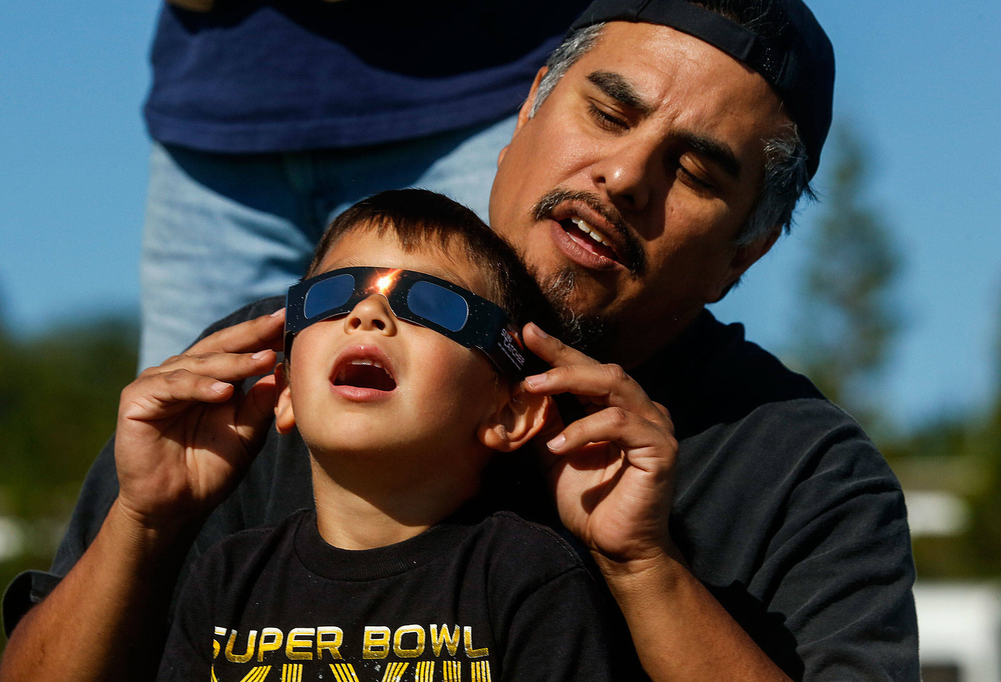 Just off Paine Field near the Future of Flight Aviation Center, Ben Flores of Mukilteo helps his sons, Vincent, 5, and Benny (back), 9, view the solar eclipse through certified safety glasses on Aug. 21. (Dan Bates / The Herald)