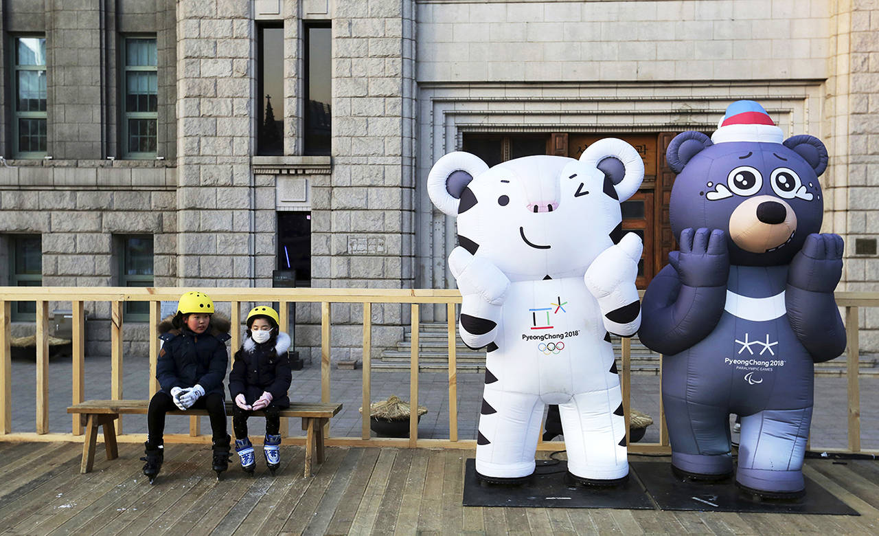 Children sit next to the 2018 Pyeongchang Winter Olympic Games' official mascots, a white tiger Soohorang, for the Olympics, and black bear Bandabi (right) for Paralympics, near Seoul Plaza Ice Rink in Seoul, South Korea, on Tuesday. (AP Photo/Ahn Young-joon)