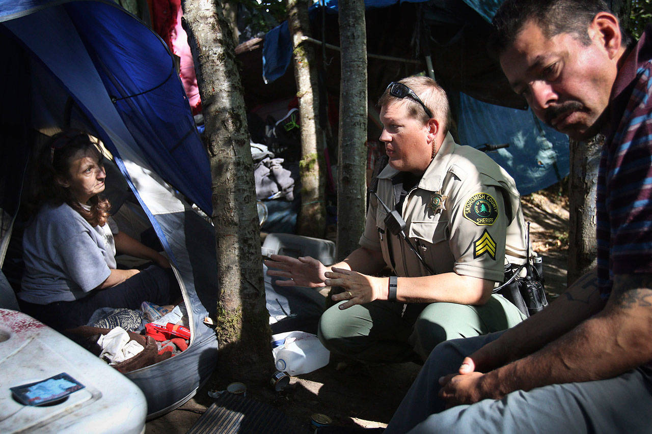 Snohomish County Sheriff's Deputy Sgt. Ian Huri speaks with Rochelle Hammond at a homeless encampment in Everett in 2015. Sgt. Huri and a social worker were working with Hammond and other residents to get them connected with detox programs, housing and other social services. (Herald file)