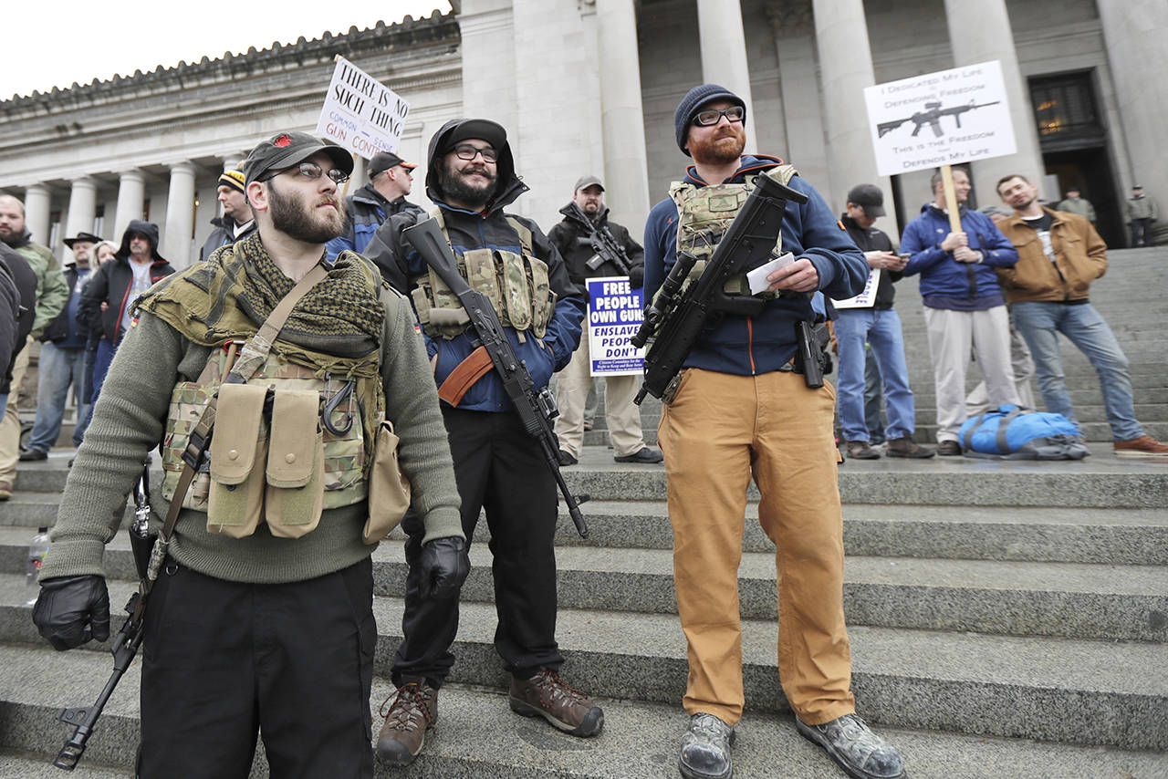 Ian Stobie (left), Jake Garza (second from left) and Ben Garrison (third from left), all of Puyallup, open-carry their guns on the steps of the Legislative Building as they attend a gun rights rally Friday at the Capitol in Olympia. (AP Photo/Ted S. Warren)