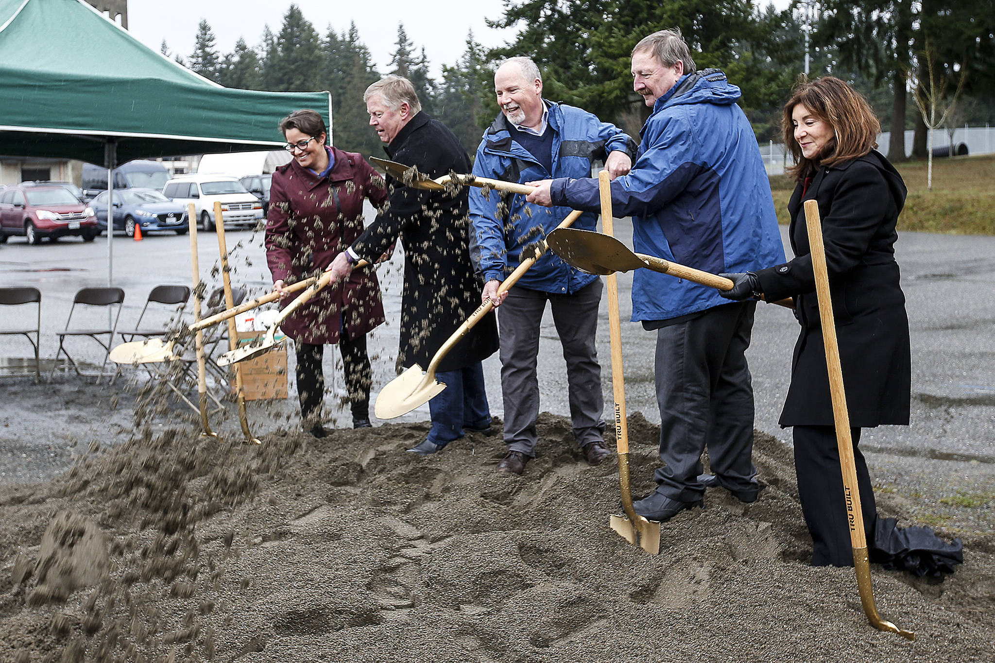 Community leaders, including Everett Mayor Cassie Franklin (left) and Snohomish County Executive Dave Somers (center right), break ground Tuesday at the site of future low-barrier housing on Berkshire Drive in Everett. (Ian Terry / The Herald)