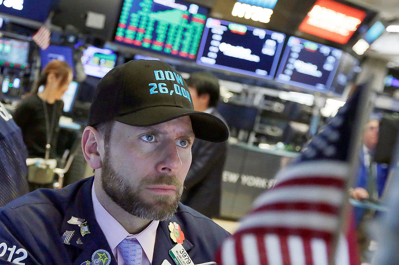 """Specialist Michael Pistillo wears a """"Dow 26,000"""" hat as he works on the floor of the New York Stock Exchange on Wednesday. (AP Photo/Richard Drew)"""